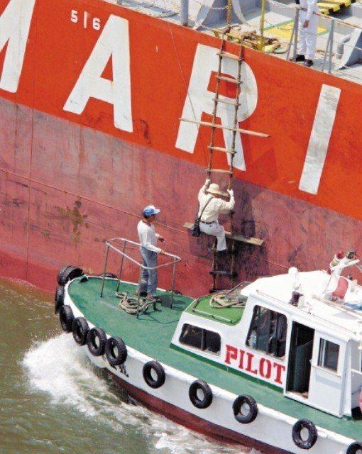 引水人搭小船出海,爬梯上大船領港,要是失手落海,不是斷手就是斷腳,風險很高。圖/...