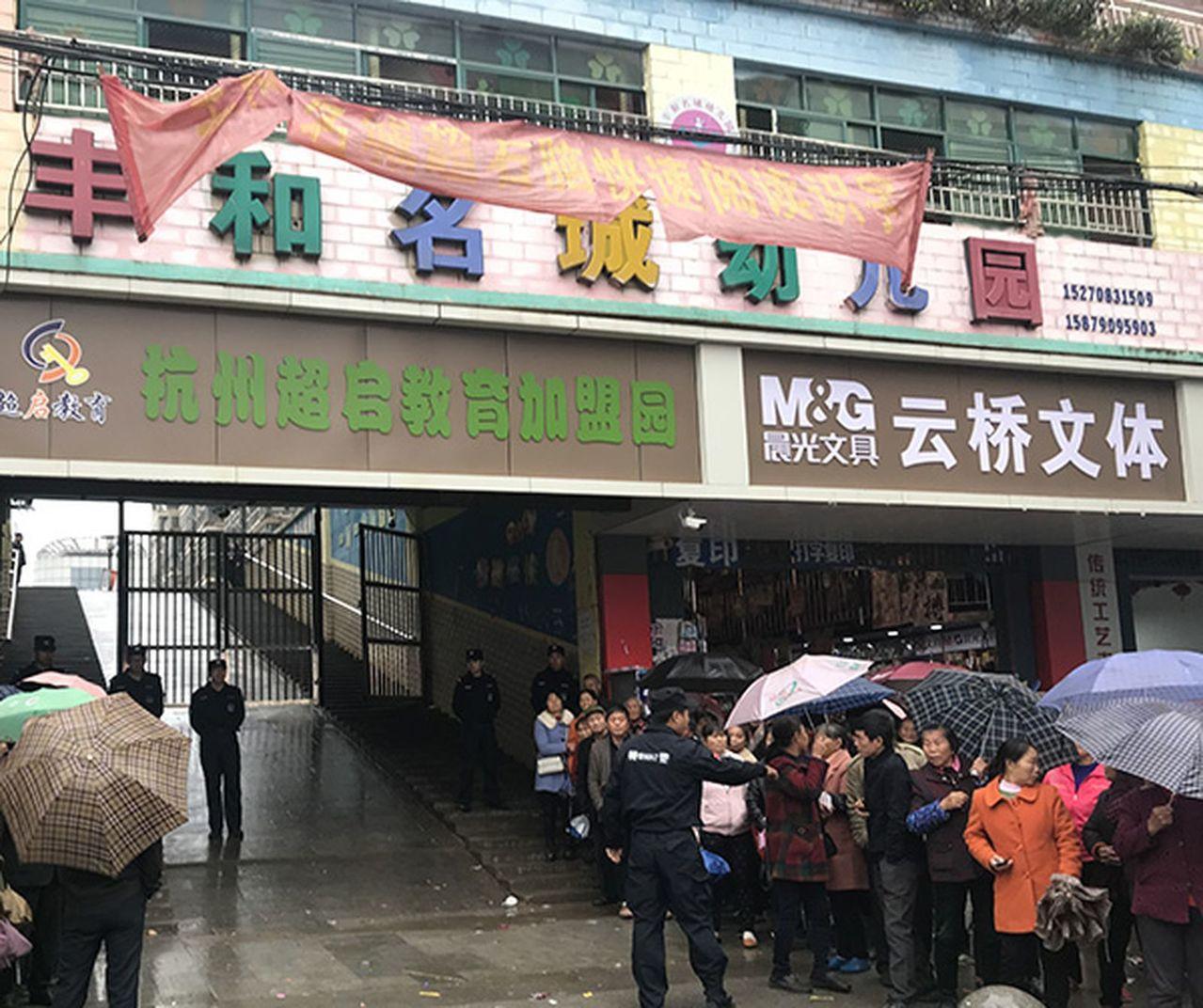 11月16日,進賢下著小雨,豐和名城幼兒園門口兩邊站著圍觀的人群。 澎湃新聞