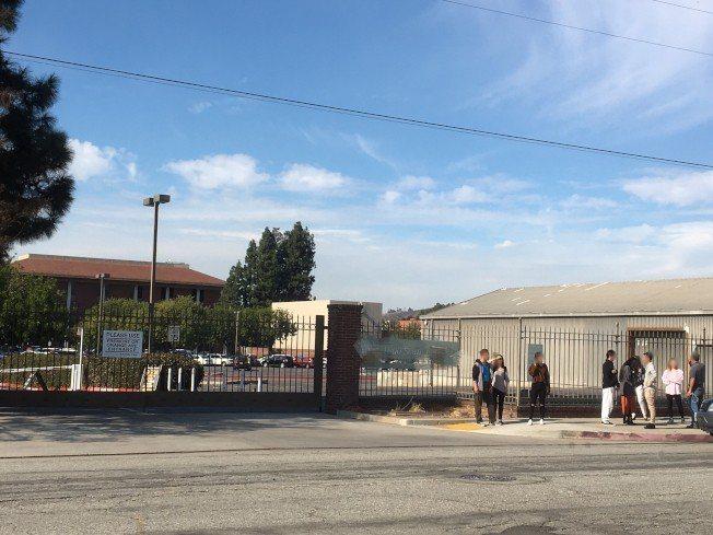 「僑報」的員工因辦公大樓被封鎖,只能在外面等待。記者謝雨珊/攝影