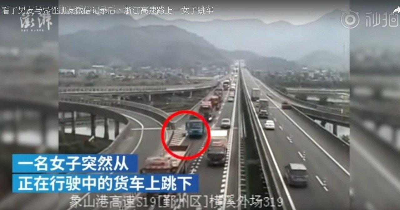 女子看完訊息後直接在高速公路上跳車。(紅圈處) 圖/取自youtube