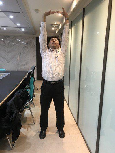 將雙手放在丹田的位置後,再手心朝上並緩緩向上向外伸展。記者簡浩正/攝影