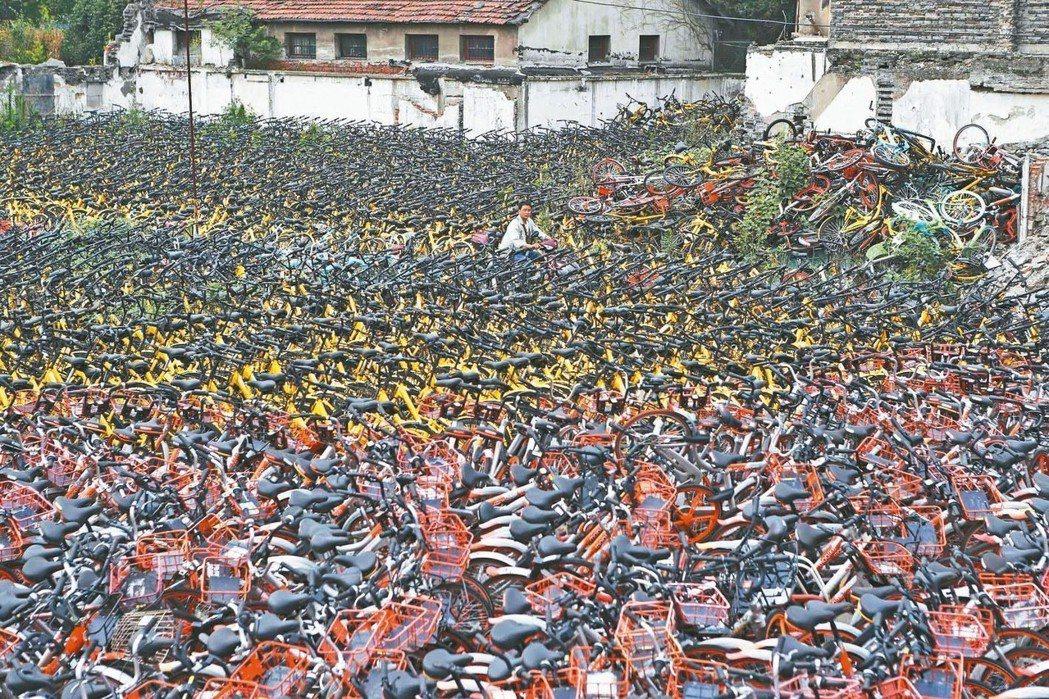 大陸一度蓬勃發展的共享單車,但如今熱潮開始退卻。圖為上海虹口區一處堆放大量遭棄置...