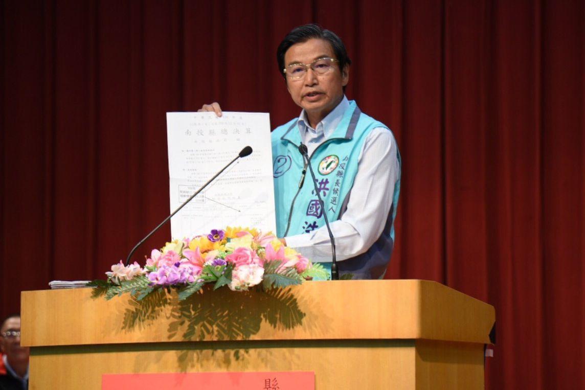 民進黨南投縣長候選人洪國浩在政見會中,提出自己準備的資料。圖/南投縣政府提供