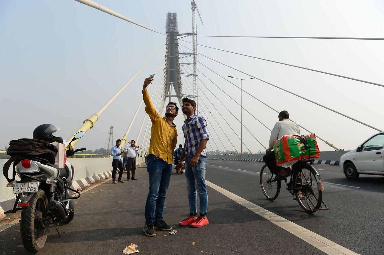 兩名男子在地標橋上的車道自拍,摩托車和腳踏車只好繞道而行。 (法新社)