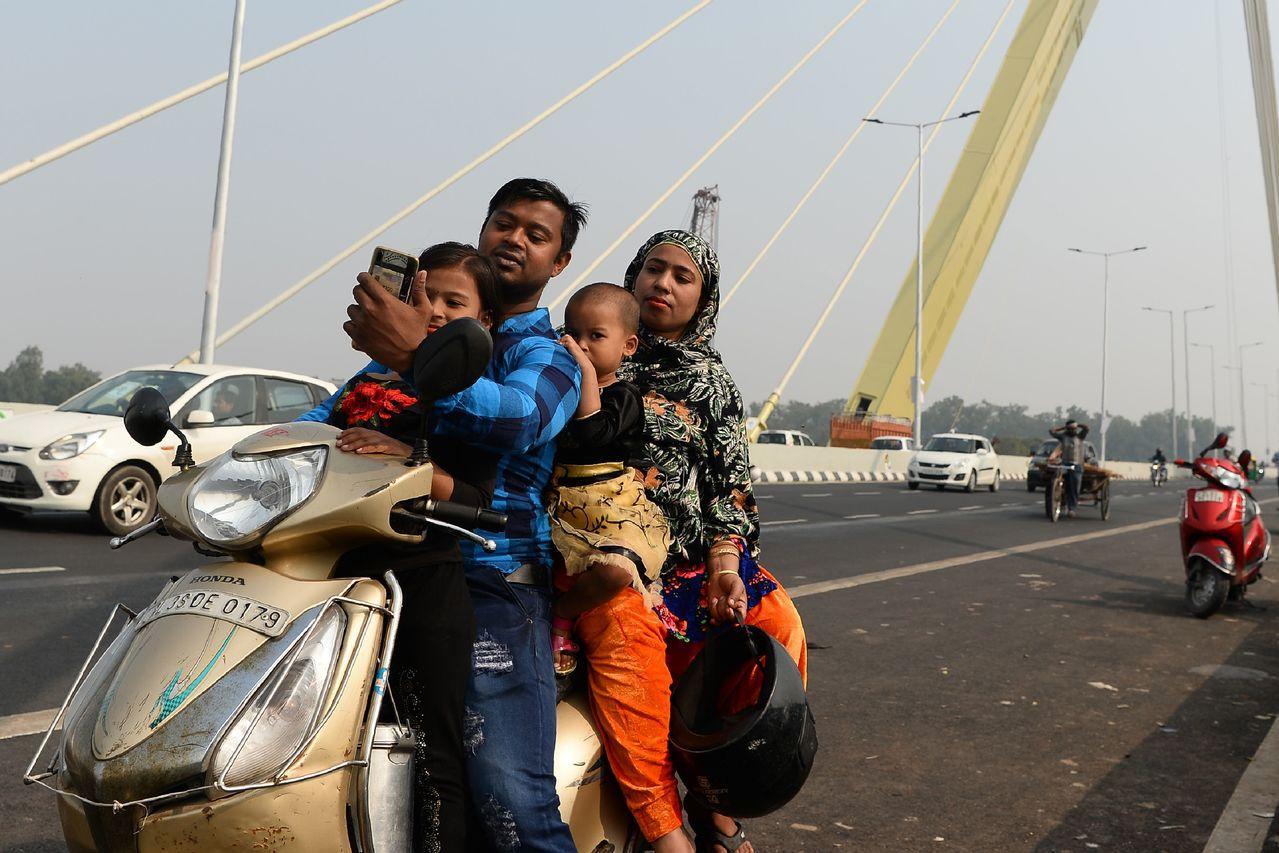 一家四口擠在一輛摩托車上,在橋上停下來自拍。 (法新社)