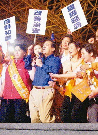 2002年,親民黨主席宋楚瑜(手持麥克風者)為泛藍團結全力支持馬英九向選民下跪。...