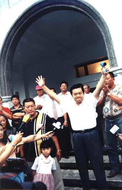 參選第二屆立委被控賄選的前花蓮市長魏木村(右)1998年報到服刑時,高舉吹風機說...