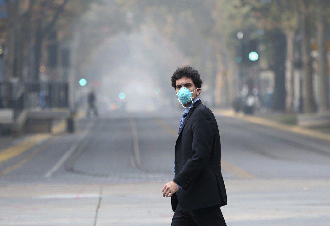 為避免吸入嗆鼻煙霧,外出民眾紛紛戴上面罩並加快腳步。圖/美聯社