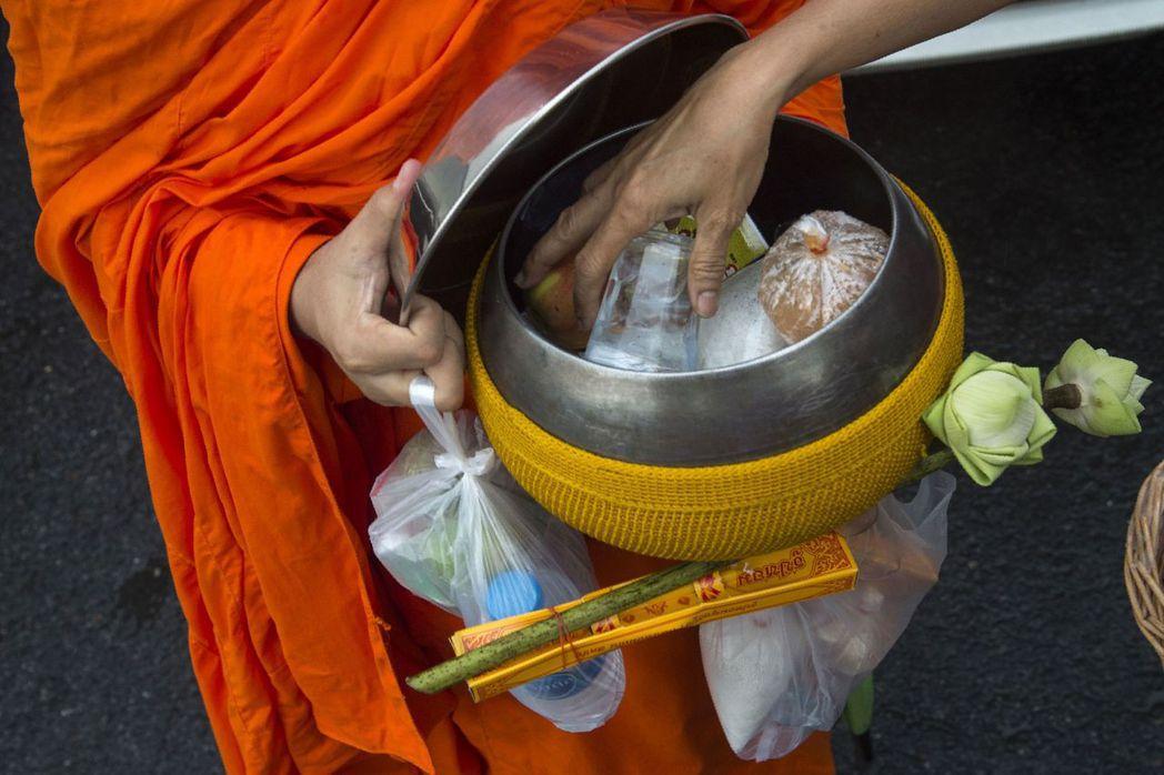 依照佛教戒律,信徒供養的食物僧侶不能拒絕。 (法新社)