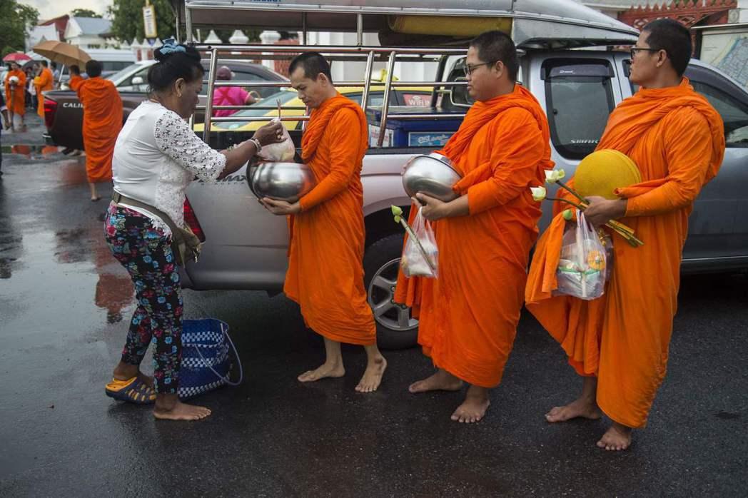 泰國僧侶清晨出門化緣,信徒把食物放進缽中。 (法新社)