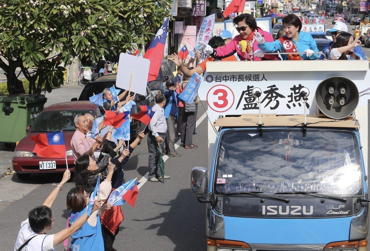 台中市長候選人盧秀燕(右)上午在大里區進行車隊掃街拜票,支持者們在路旁揮舞著旗幟...
