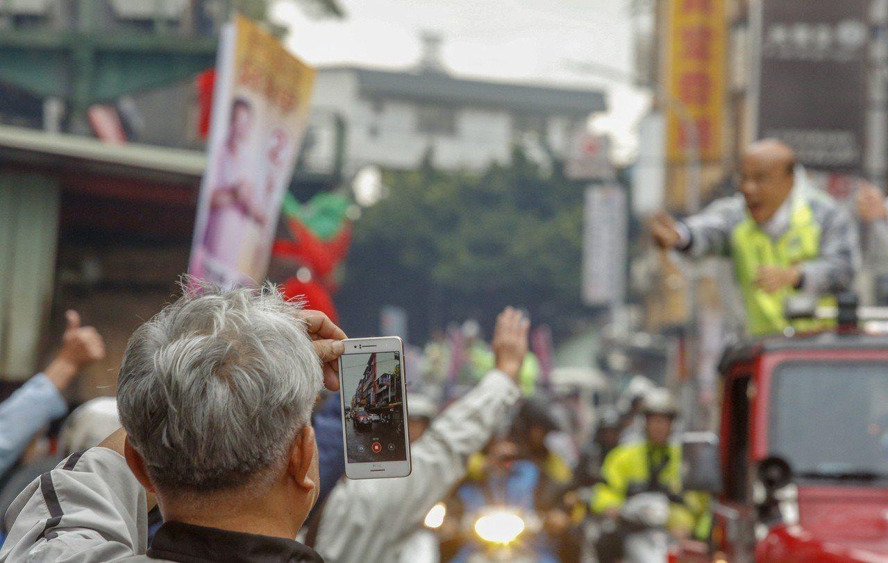 民進黨新北市長候選人蘇貞昌(右)上午以車隊在新莊區掃街拜票,支持者用手機記錄下這...