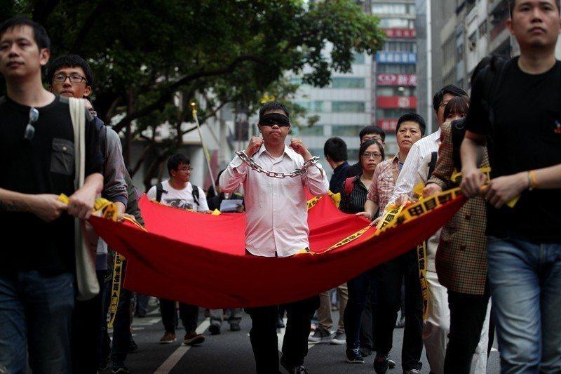 2017年,台灣公民李明哲被中國控以「顛覆國家政權罪」而遭逮捕,迄今仍身陷中國黑牢。圖為2018年3月,台灣民眾發起的聲援遊行。 圖/歐新社