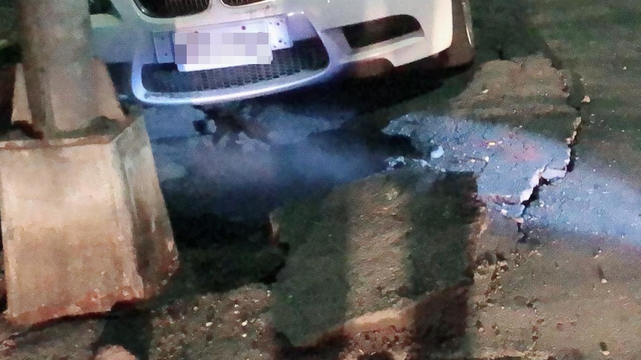 高雄市前金區光復三街人孔蓋冒煙,消防隊打開人孔蓋時,路面出現裂痕。記者林保光/翻...