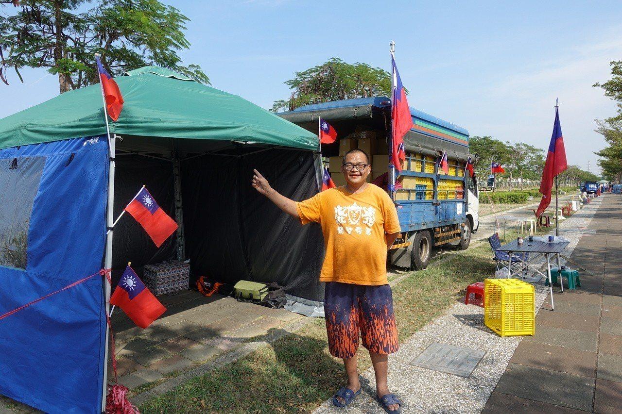 攤商鍾大哥在現場顧攤,現場搭好帳篷,插著國旗,預計今晚要在這邊過夜。記者劉星君/...