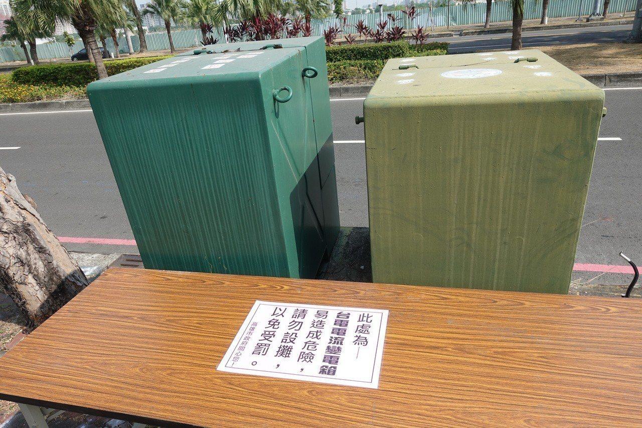 有攤商在變電箱擺桌子,高市府貼上公告提醒在變電箱旁邊不要擺攤,以免受罰。記者劉星...