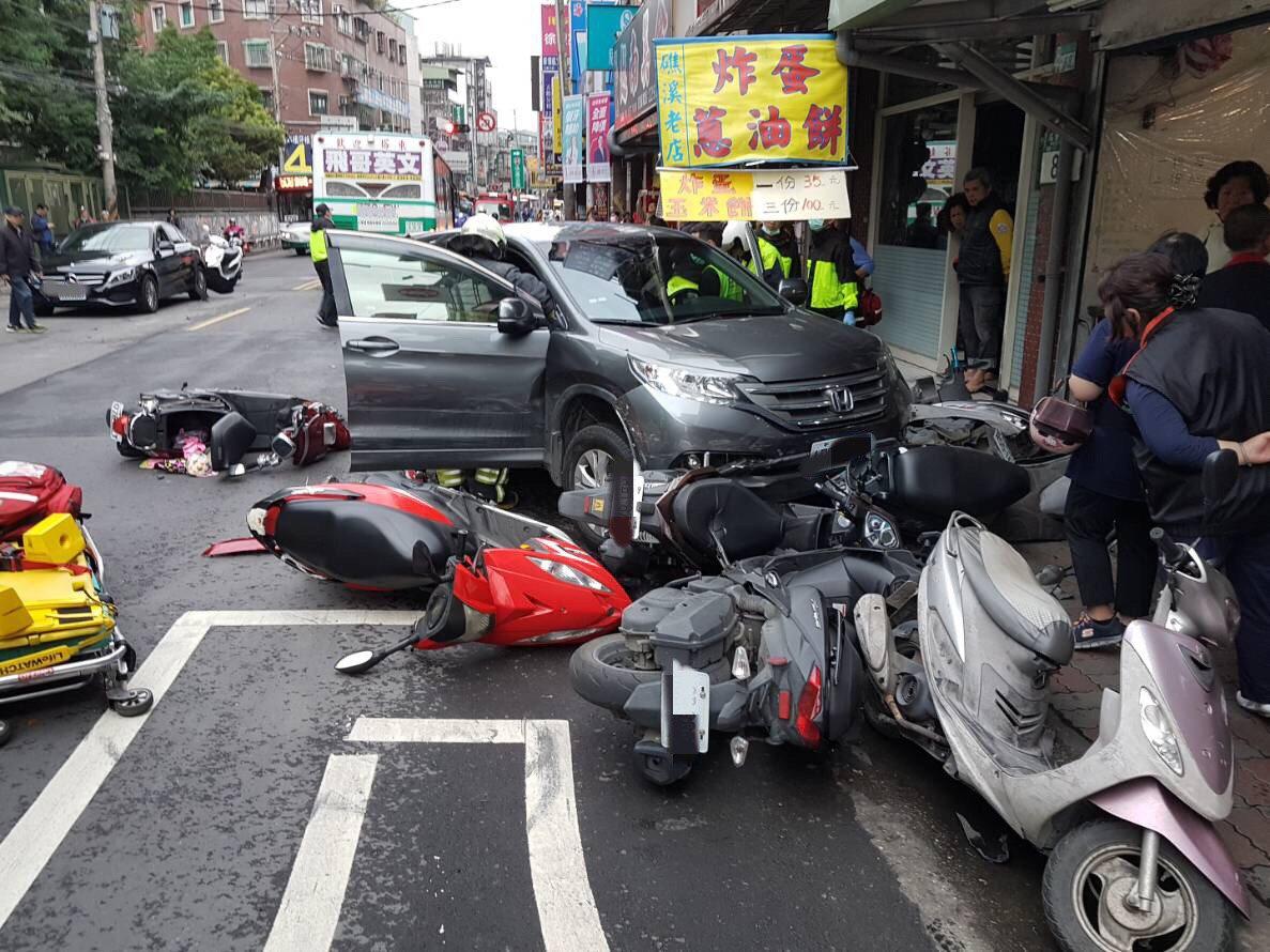 車禍現場一片狼籍,多輛機車被撞倒在地,還波及路過的轎車和公車。記者巫鴻瑋/攝