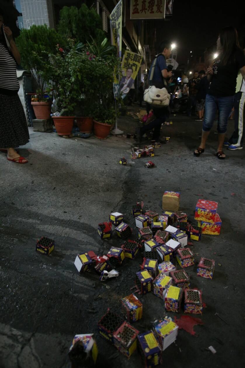 現場路邊擺放燃放後的鞭炮,附近民眾趕緊將鞭炮收拾裝袋。記者劉學聖/攝影