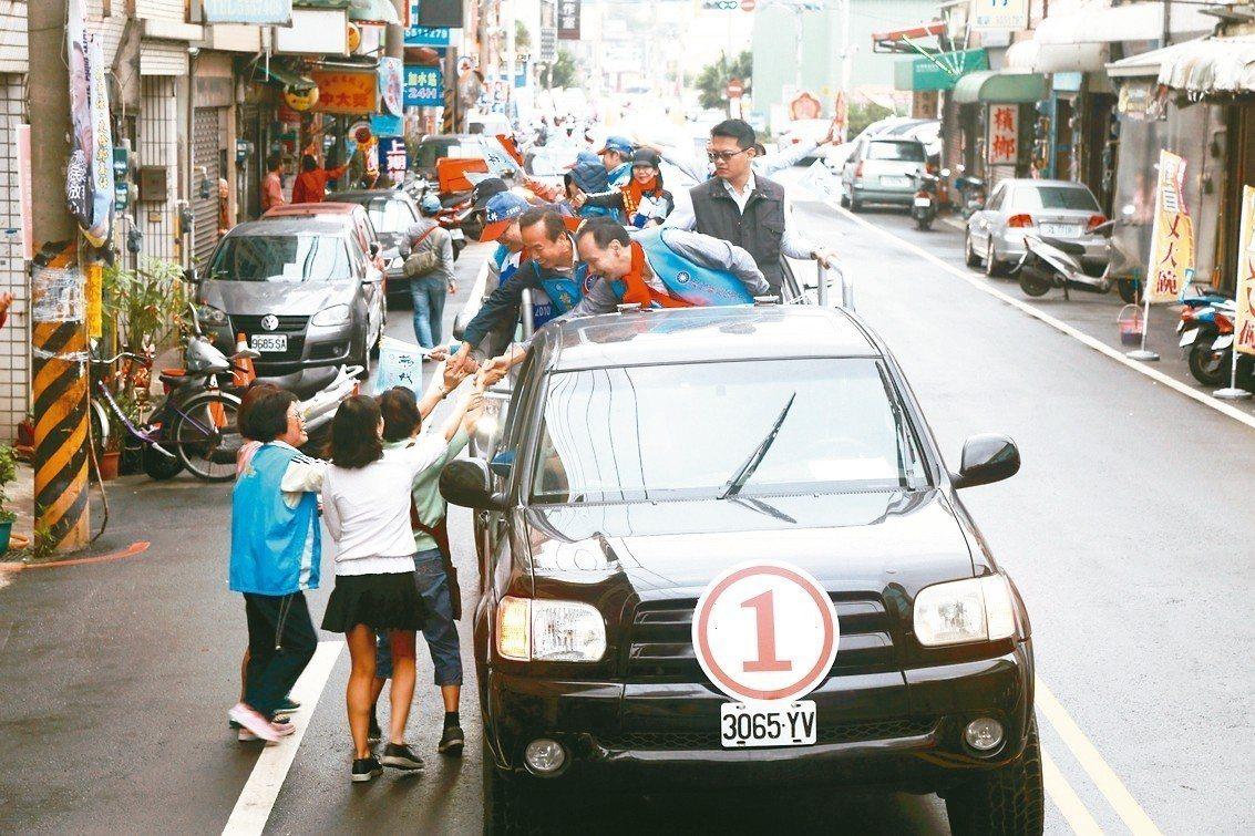 國民黨新竹縣長候選人楊文科車隊掃街,不少民眾衝出家門搶著握手。 記者郭宣彣/攝影