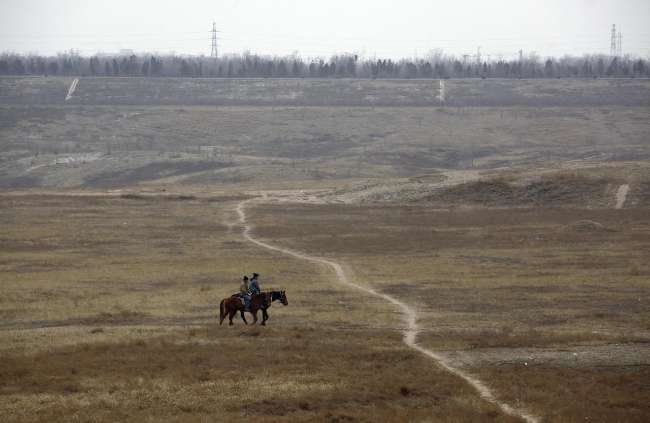 兩名男子在北京郊外永定河乾涸的河道上騎馬。路透