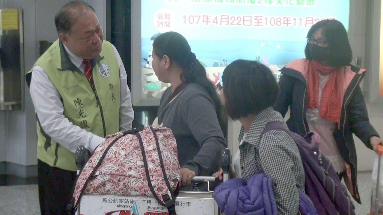 爭取連任的澎湖縣長陳光復(左一)一早前往馬公機場為返鄉旅客接機,爭取支持。記者王...