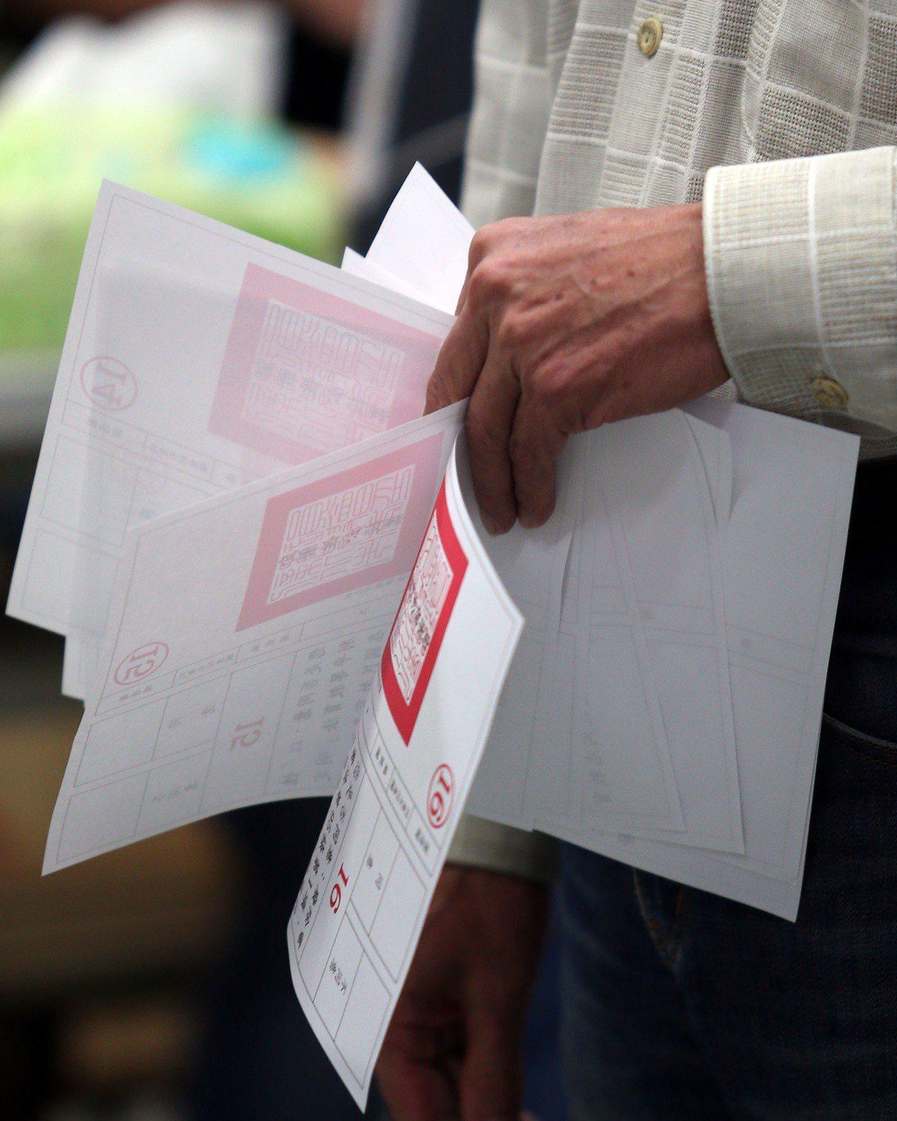 九合一大選今天上午開咍投票,由於今年最多有十三張選票,民眾手上拿著十張公投票等著...