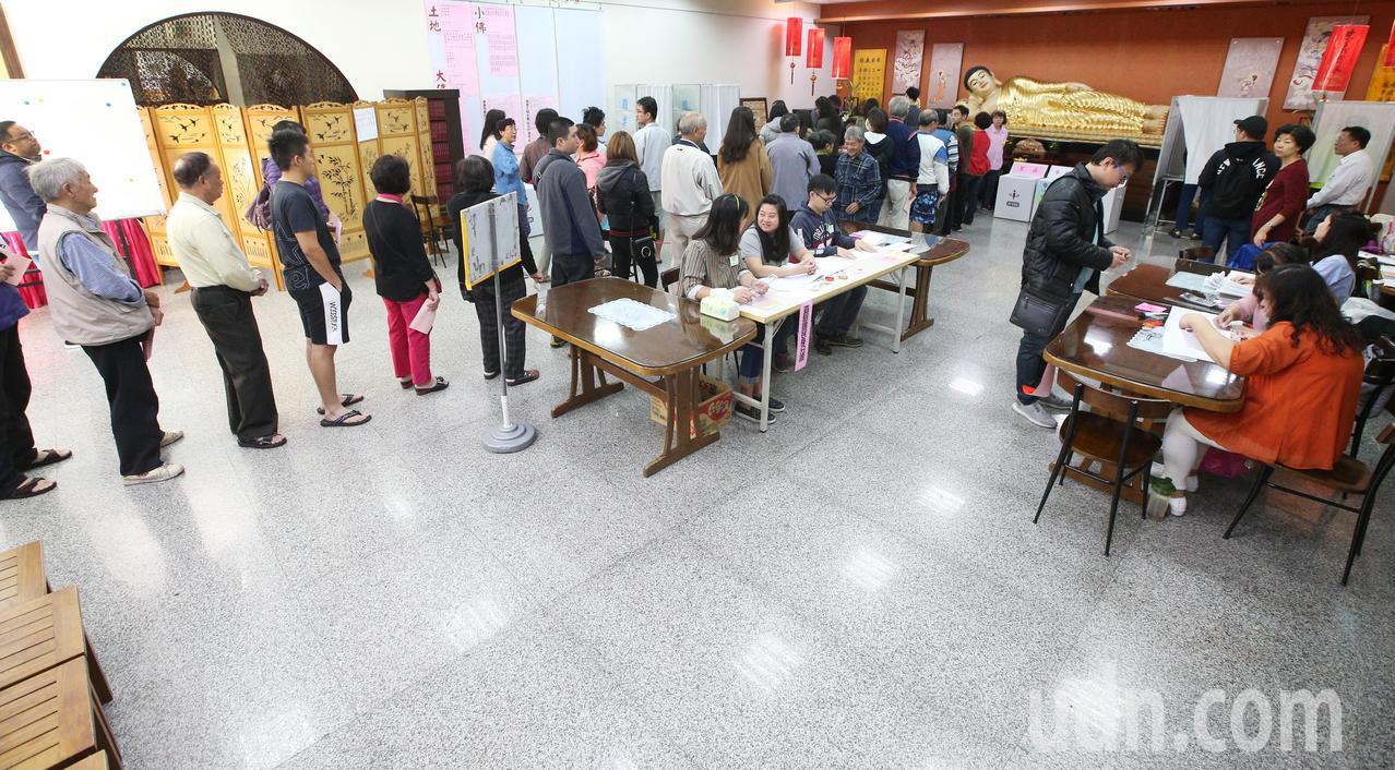 九合一選舉與10案公投上午開始投票,由於公投案有十案,投票所內排隊領公投票的民眾...