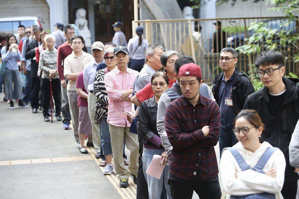九合一選舉與十案公投上午登場,一早天氣放晴,投票所外排滿準備投票的民眾。記者余承...