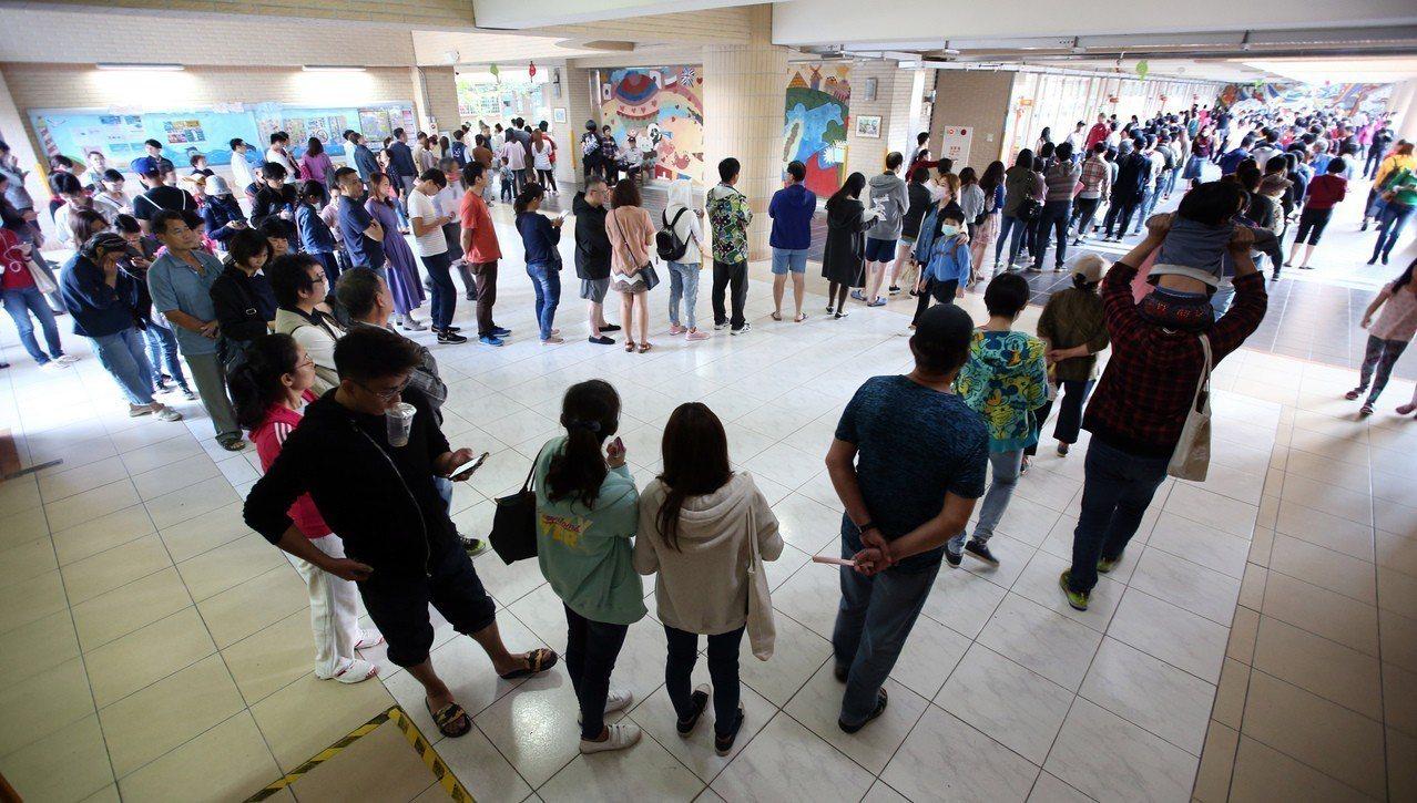 九合一大選投票,各地投票所都出現大排長龍的景象,連校門外兩側都還是排隊的人潮。...