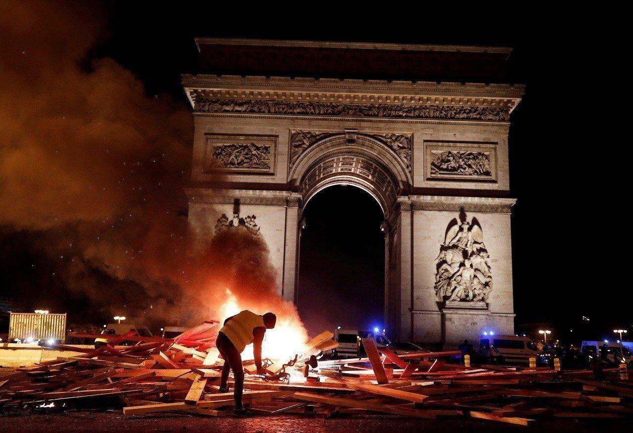 法國各地24日出現最新一輪的反油價調漲示威抗議,一名抗議者在首都巴黎的香榭麗舍大...
