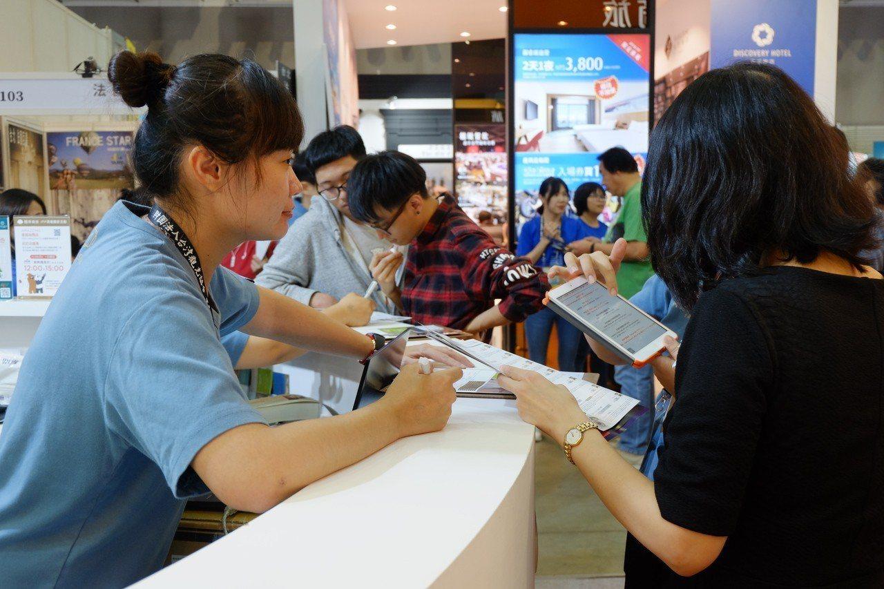 國泰商旅的展位前,許多民眾來詢問購買餐券及住宿券。記者韓化宇/攝影