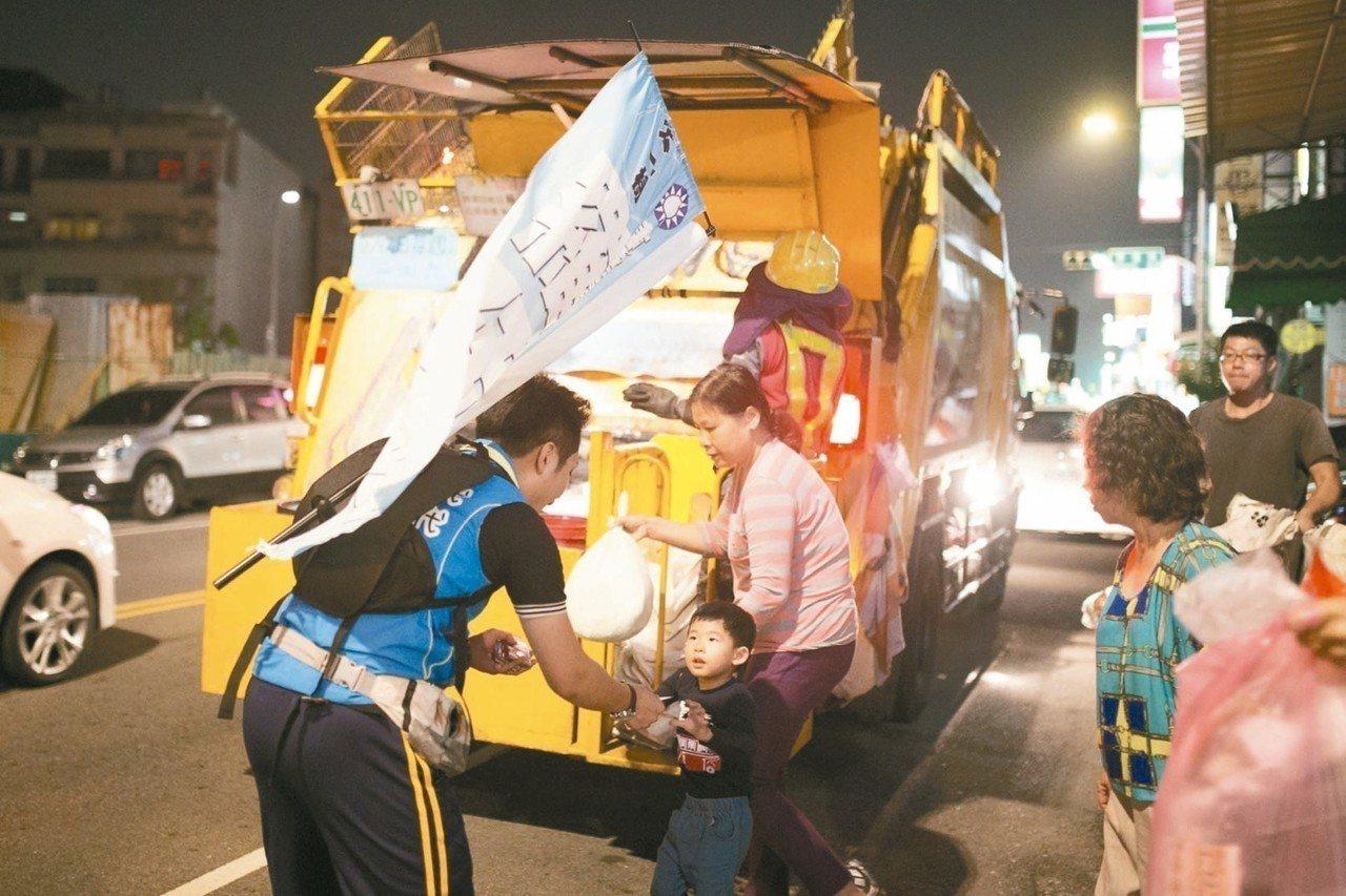 台中市議員當選人羅廷瑋(揹旗者)長期追著垃圾車跑,與選民近距離拜票。 圖/羅廷瑋...