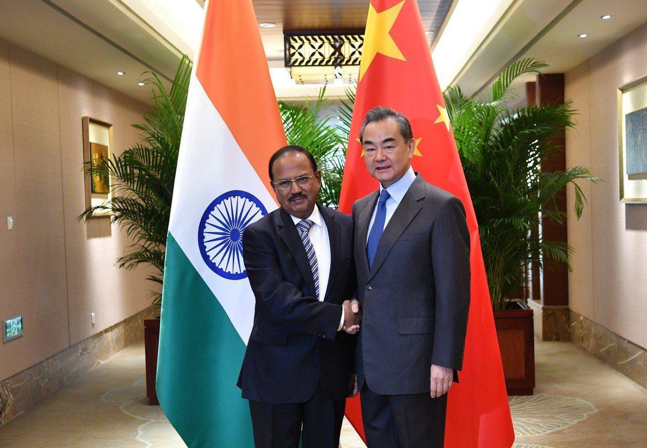 中國國務委員兼外交部長王毅(右)與印方特別代表國家安全顧問多瓦爾(左),24日在...