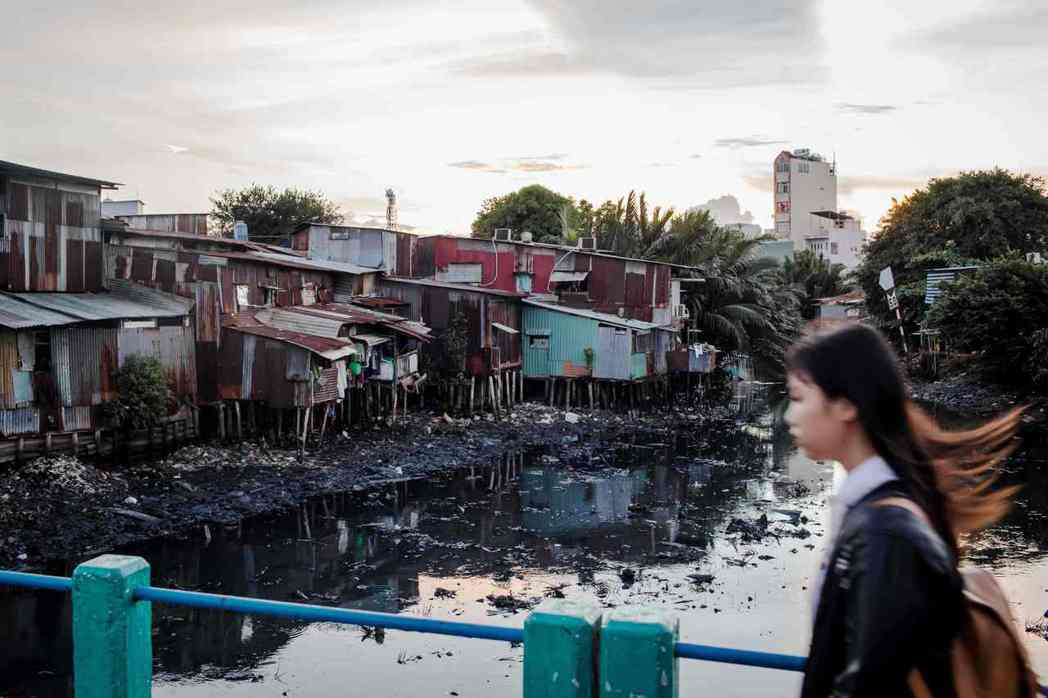 胡志明市的運河上漂浮著垃圾,河水髒臭發黑。圖/法新社