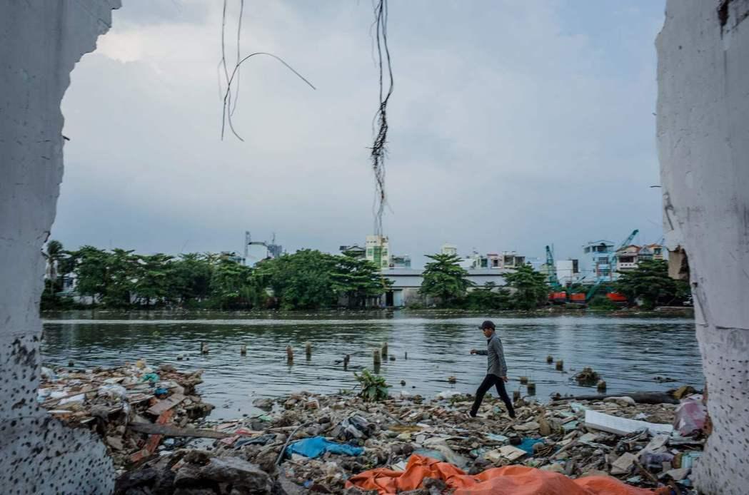 一名男子走過最近拆除的黑色運河畔破陋屋。圖/法新社