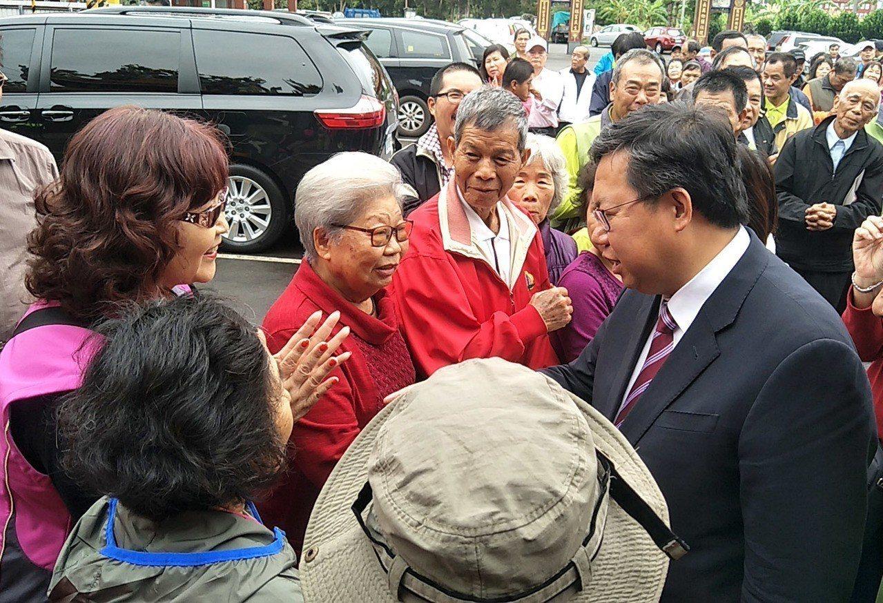 桃園市長鄭文燦(右)返鄉祈福謝票,看見他母親(左二)在人群裡趕快上前握手問候。記...