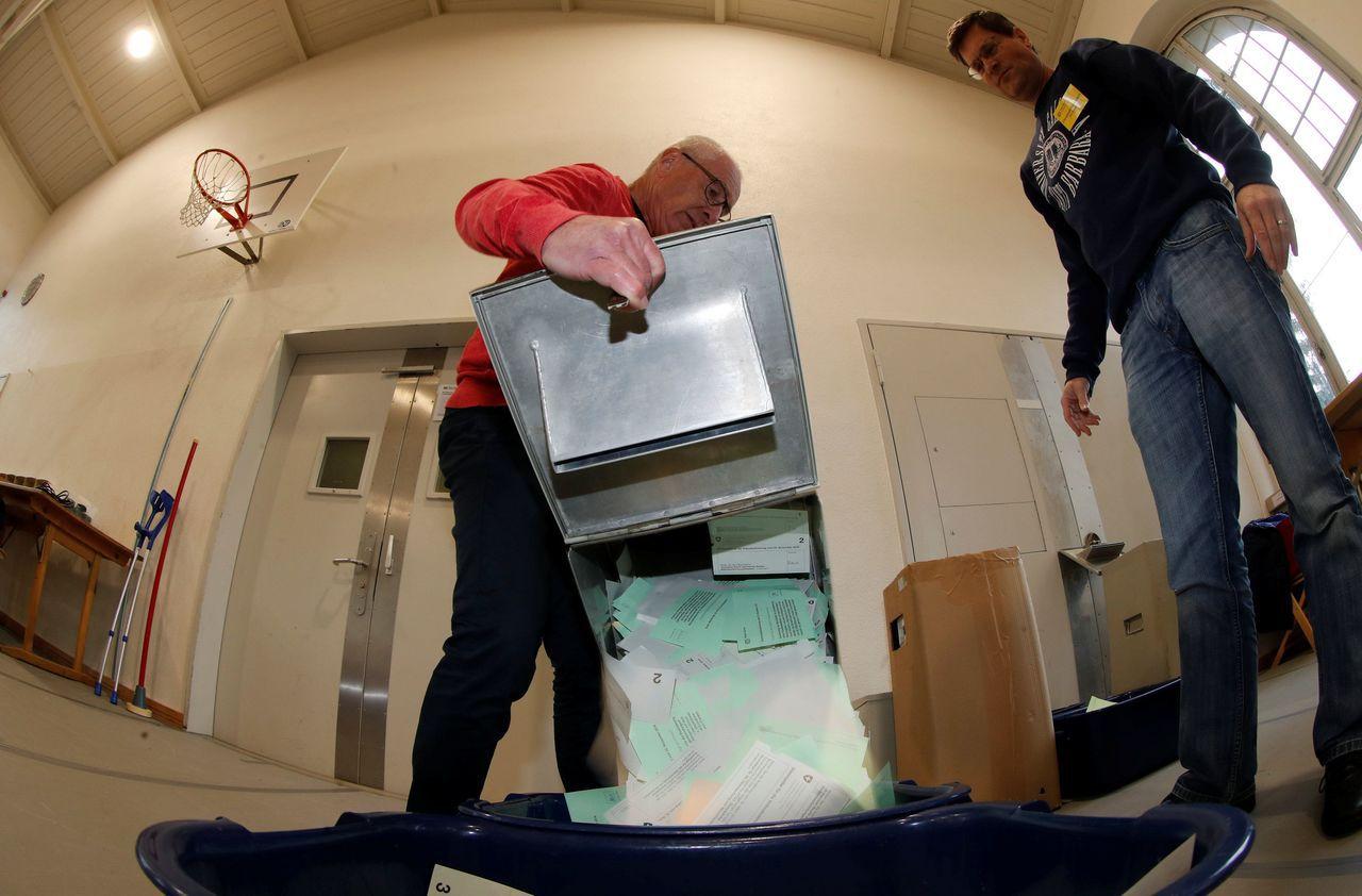 瑞士25日公投後選務人員騰空票匭。路透