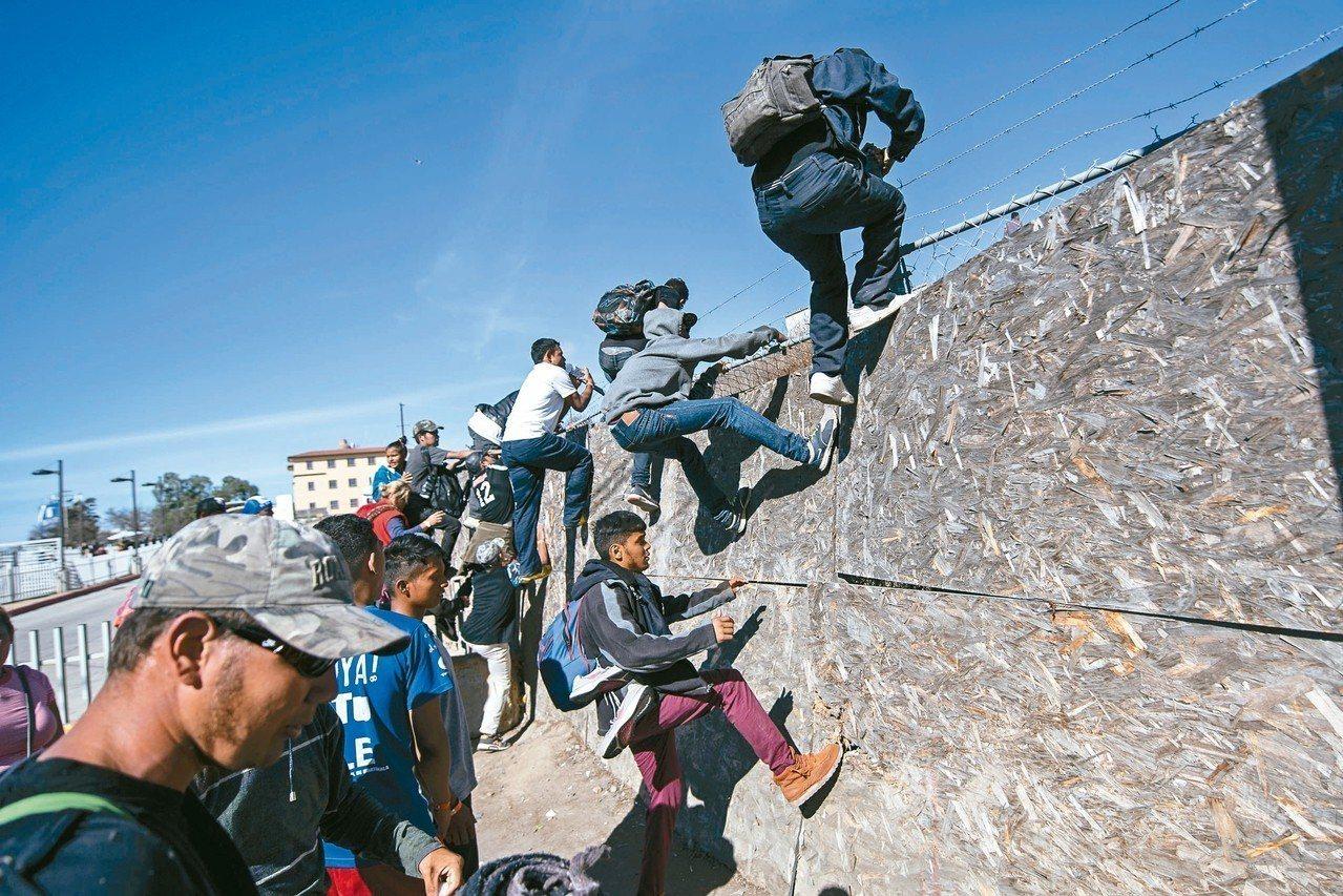 大批中美洲無證移民廿五日強行越過美墨邊界高牆,意圖進入美國。 (美聯社)
