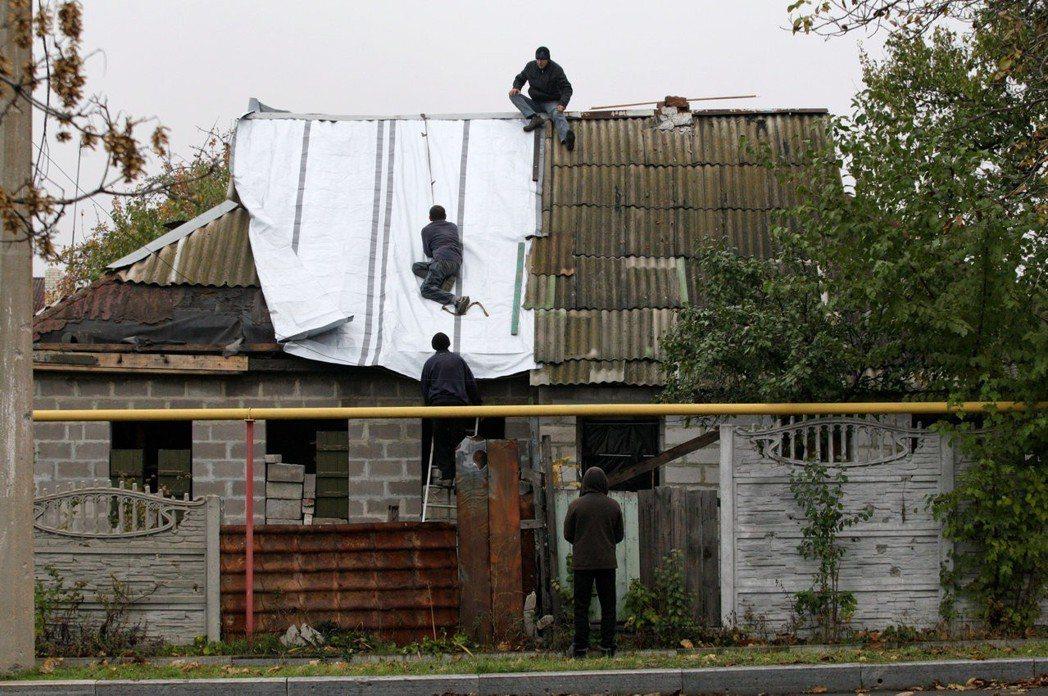 頓內次克居民修理遭戰火破壞的屋頂。 (路透)