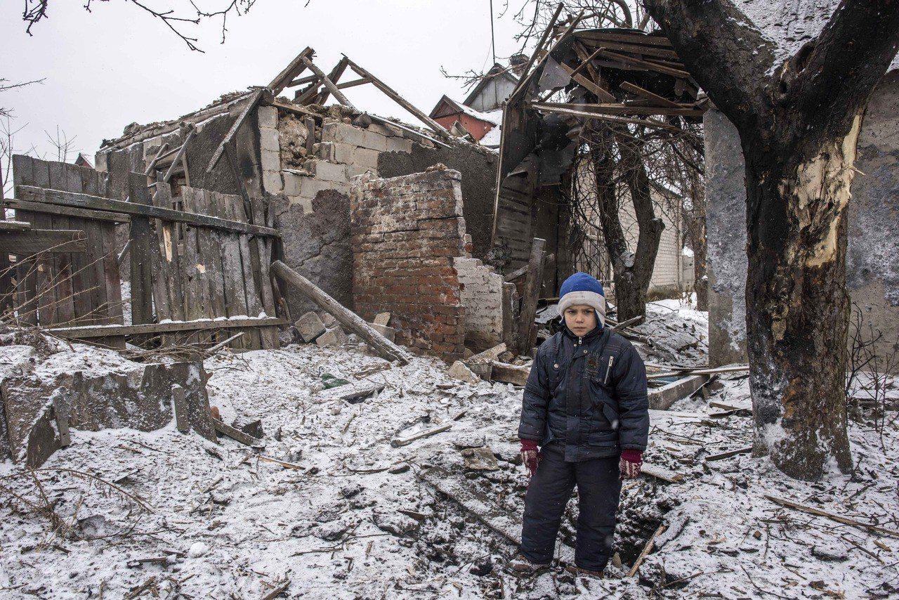 在接近前線的烏克蘭阿夫傑夫卡市,一個8歲男孩站在被砲彈炸毀的家門口。 (美聯社)