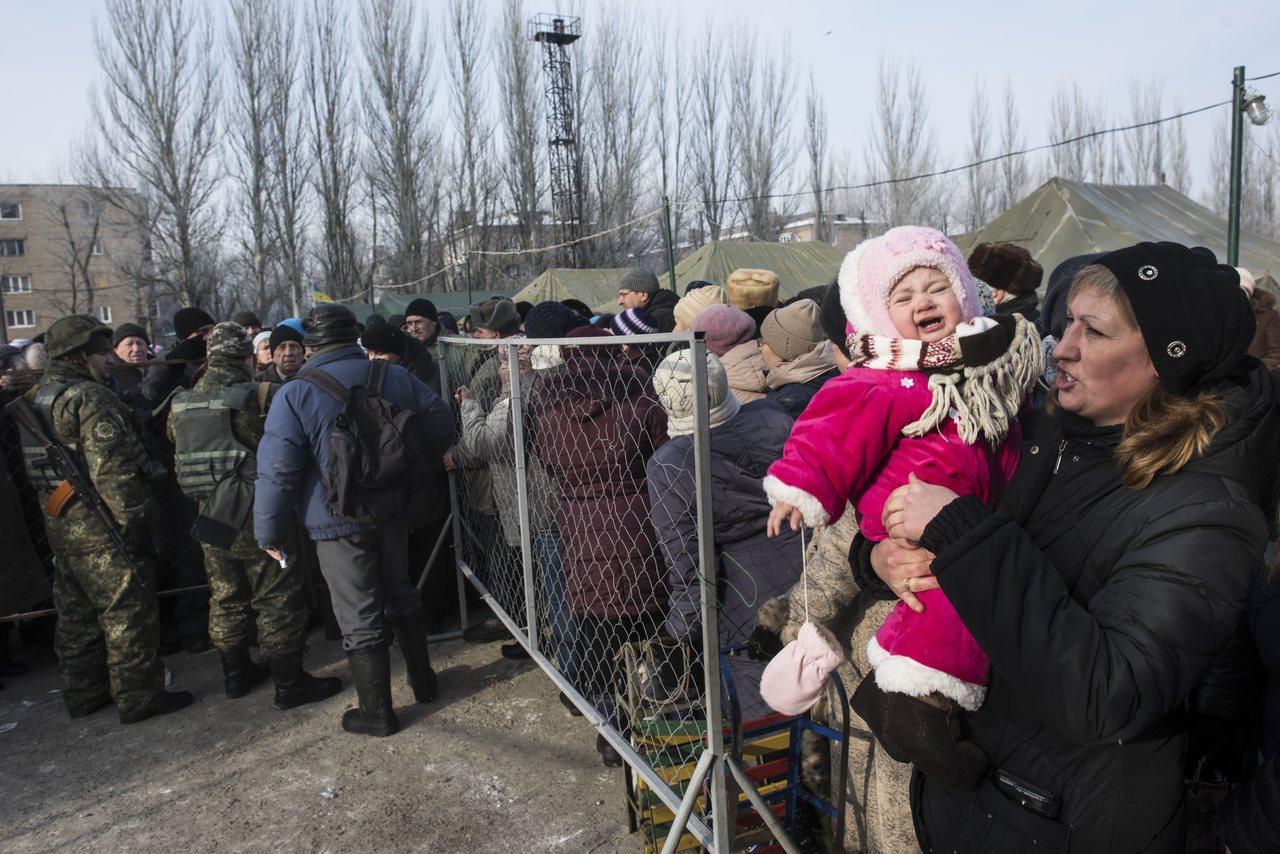在烏克蘭東部接近前線的阿夫傑夫卡,一個女子抱著小孩排隊等待領取糧食等物資。 (美...