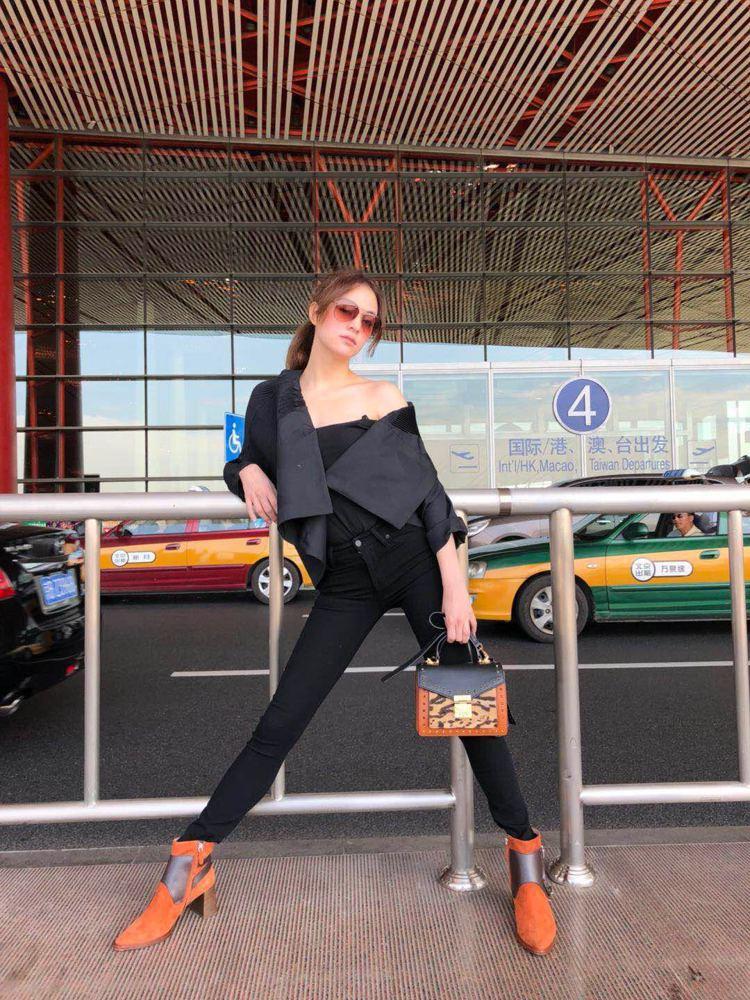 張榕容以少見的誇張肢體表現機場時尚,配襯MCM包款。圖/MCM提供