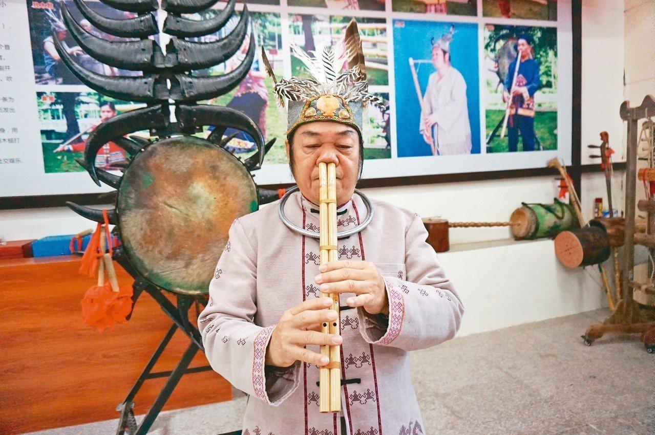 保亭國家級黎族竹木器樂代表性傳承人黃照安,示範用鼻子吹的特殊樂器「鼻蕭」。 記者...