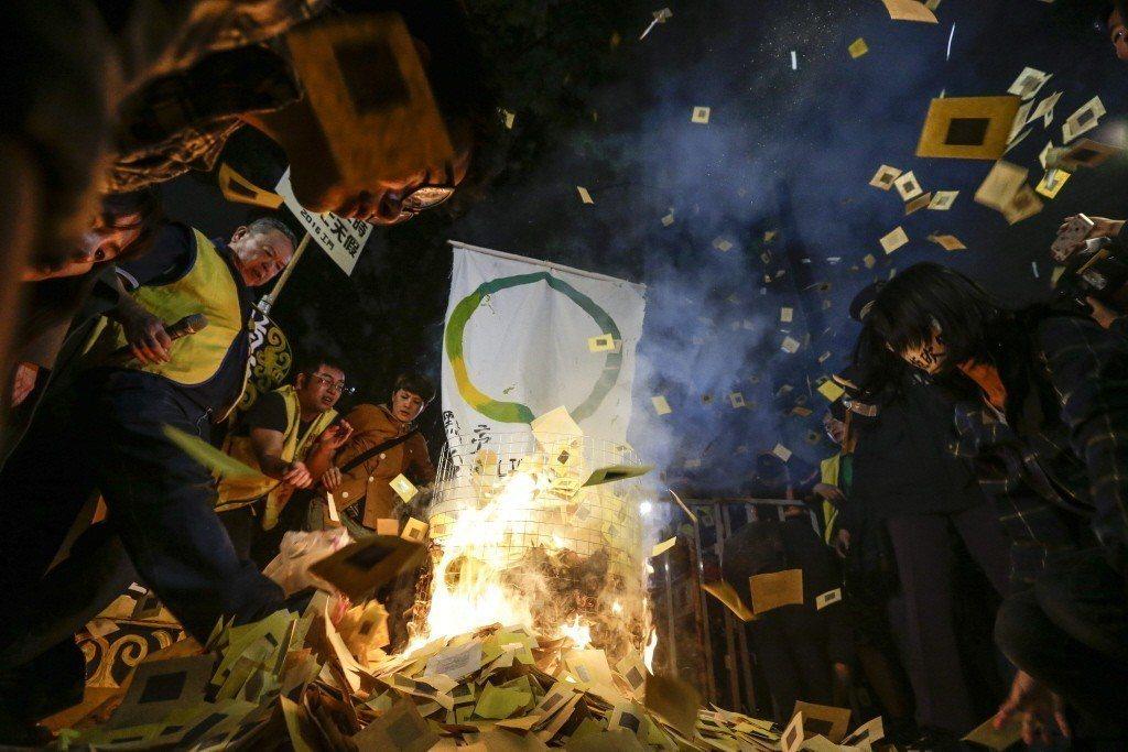 民進黨上台後第一次修惡《勞基法》,民團焚燒競選標語「點亮台灣」,表達不滿。 圖/...