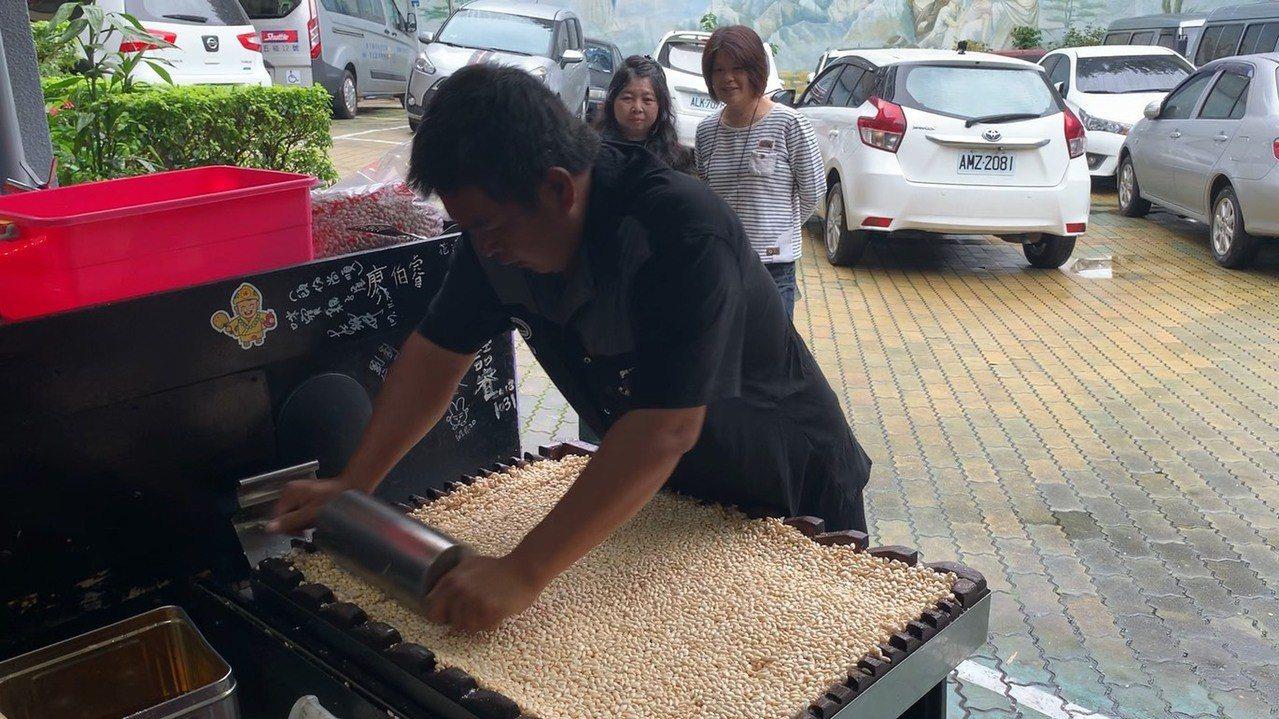 熟練的將爆好的米倒進盆子,加入熬煮好的麥芽糖攪拌,再將它倒進四方形的模型裡用滾筒...