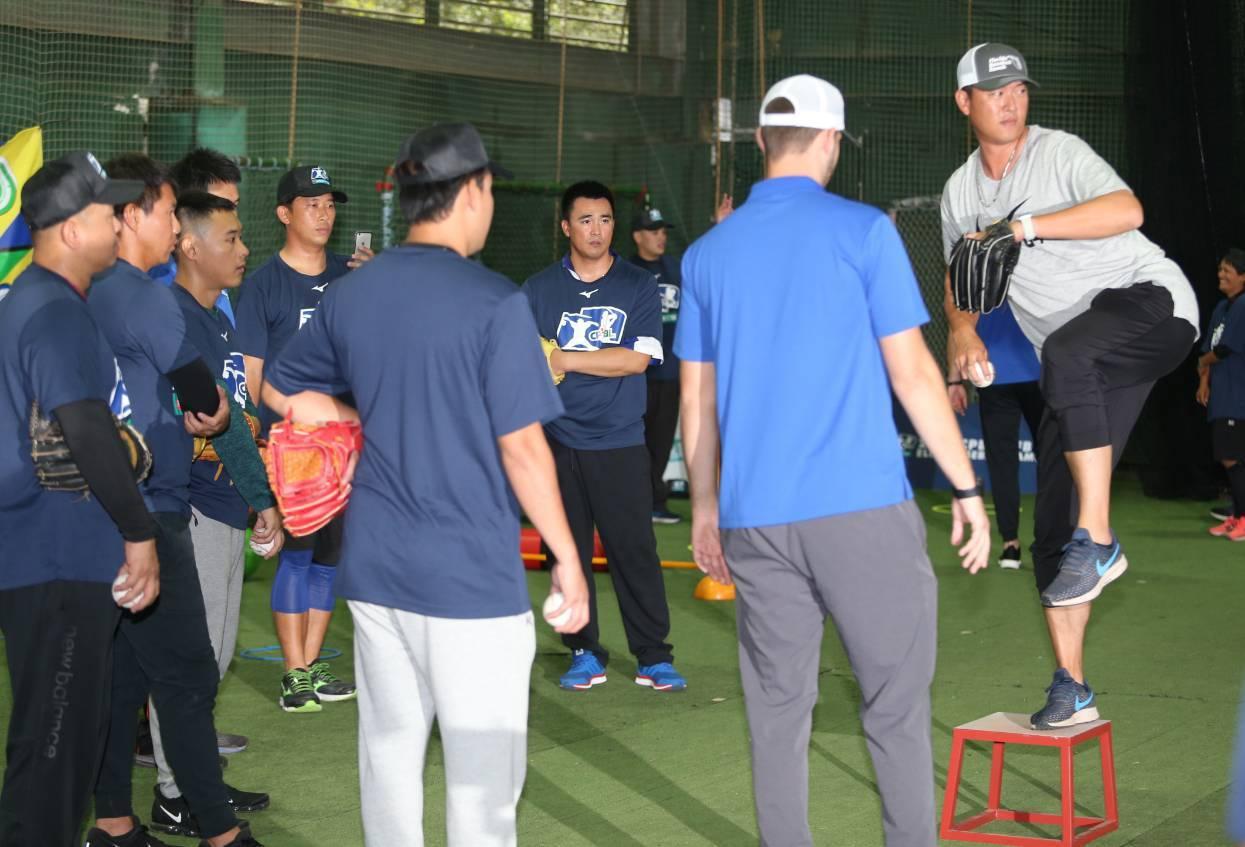 3名香港教練和其他學員一起看王建民(右)示範投球動作。記者侯永全/攝影