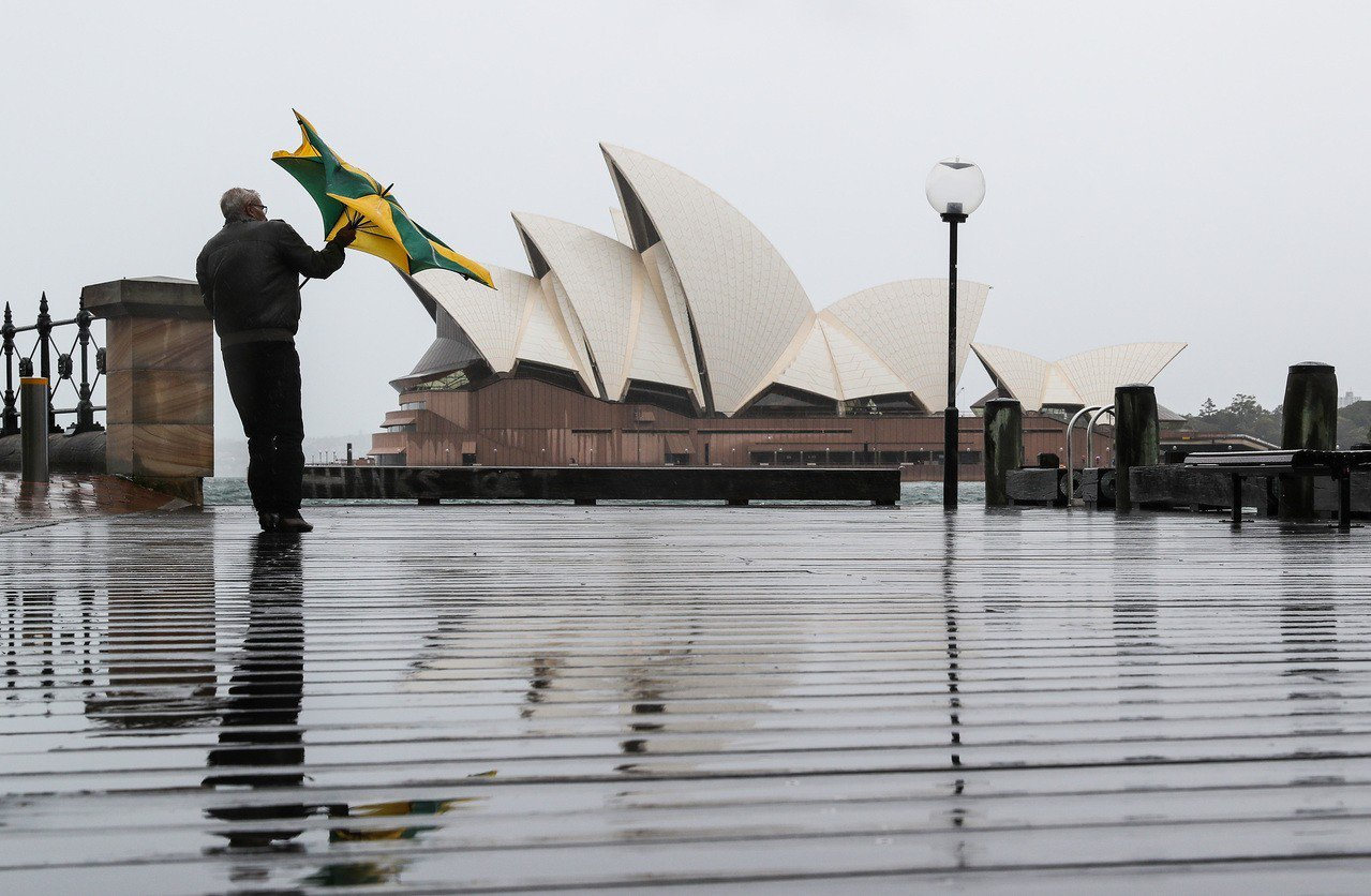 雪梨狂風大作,一名男子手中的傘被吹到開花。(新華社)