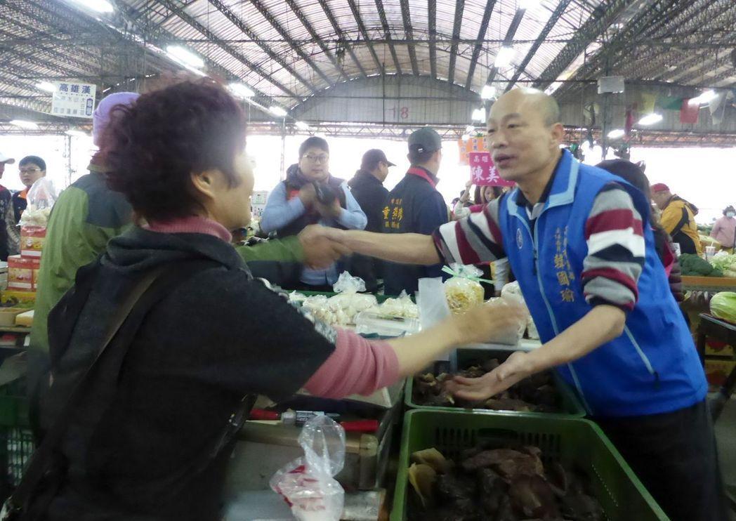 準高雄市長韓國瑜(右)就任首日將夜宿果菜市場,代表不忘本;圖為今年農曆過年期間,...
