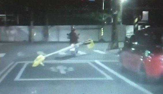 一名男子騎機車載運多根超長的大竹竿,就綁在機車一側拖行著,橫在整條馬路上。圖/ ...
