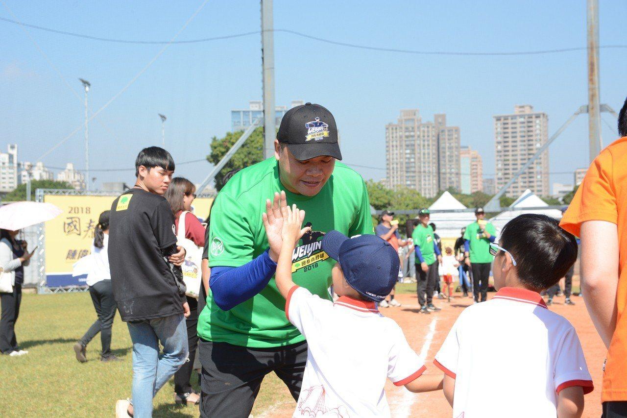 陳偉殷棒球訓練營首度舉行親子棒球賽,職業球星教練團與小朋友親切互動。記者蘇志畬/...